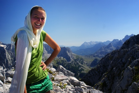 Hiker woman at mountain top summit smiling and mountains in background photo