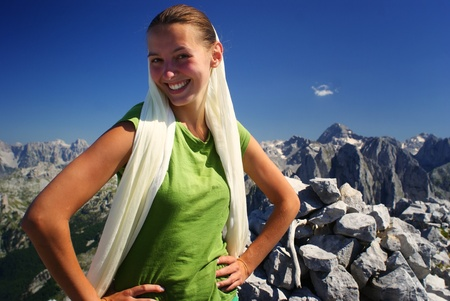 Hiker woman at mountain top summit smiling and mountains in background