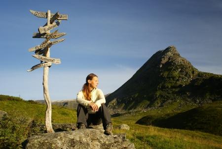 시골에서 등산객 여성은 나무 표지판에 앉아 스톡 콘텐츠