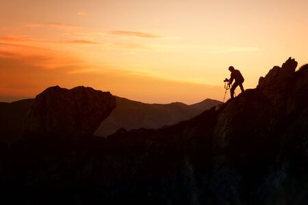 silhouette of a photographer who shoots mountains