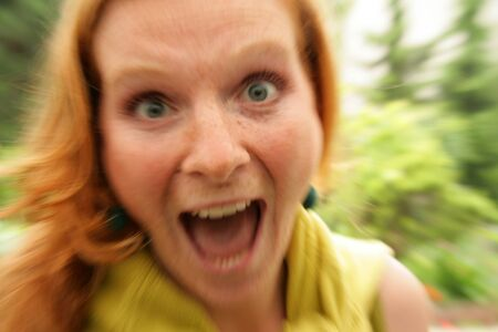 Portrait of screaming redhead girl accented by zoom effect