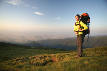 Hiker women standing in the mountains in the sunset