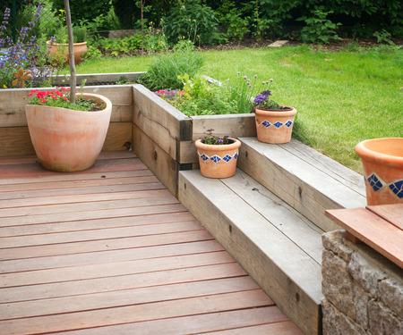 Tuin detail met terras met houten trap en bloemen in bloempotten. Stockfoto