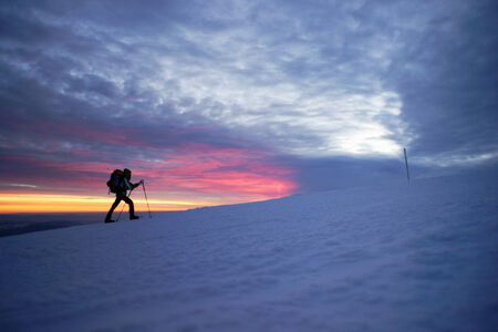 Man walking in the mountains by sunset