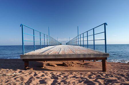 Wooden pier leading to sea Stock Photo