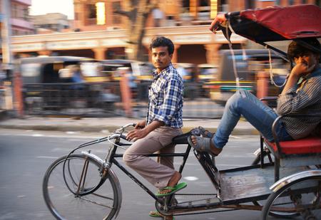 Rickshaw rider transports passenger at evening sun Editorial