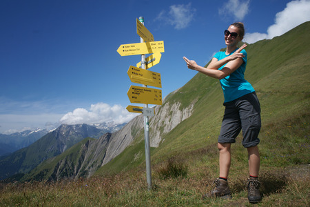 Hiker woman showing directions next to signs Stock Photo
