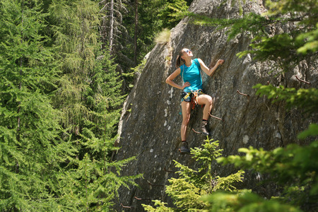 treetops: Young woman climbing in via ferrata among the treetops