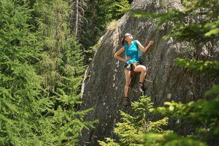 Young woman climbing in via ferrata among the treetops