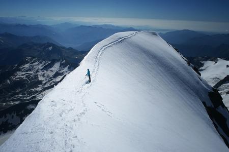 Climber women on a summit ridge of mountain