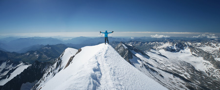 Woman on a mountain summit, moment of a success, reaching a top of a mountain Stock Photo