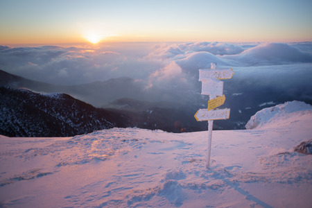 Sunrise in snowy mountains above the clouds, pinky reflections, orientation signs in foreground