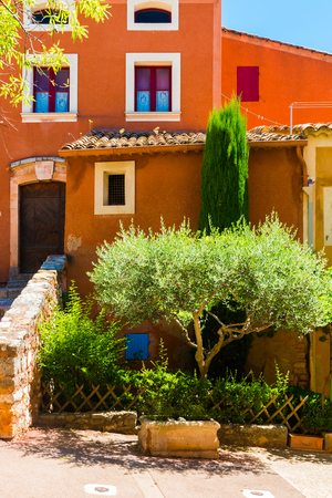 Colorful ochre houses and garden in the Roussillon village in Provence, France