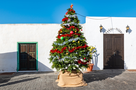 Christmas tree in front of the typical white houses and blue sky, Teguise, Lanzarote, Canary Islands, Spain. Фото со стока