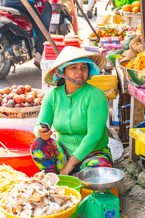 Vietnam, Phu Quoc Island, 26 February 2018: Unidentified women with typical vietnamese conical hats sell fresh food on a street market with chaotic traffic jam
