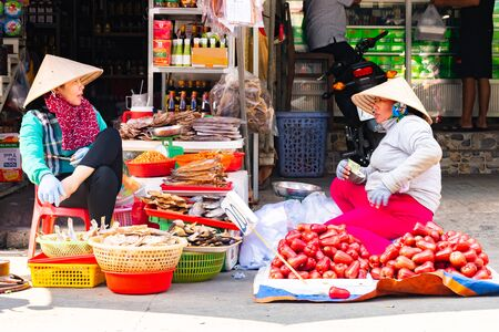 Vietnam, Phu Quoc Island, 26 February 2018: Smiling unidentified women with typical vietnamese conical hats sell fresh food on a street market