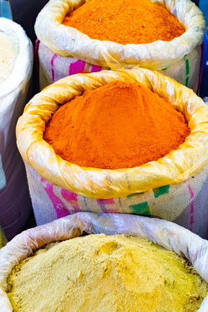 Colorful spices powders of curry and chilli traditional spicy street market in New Delhi. India