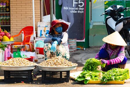 Vietnam, Phu Quoc Island, 26 February 2018: Unidentified women with typical vietnamese conical hats sell fresh food on a street market Redakční
