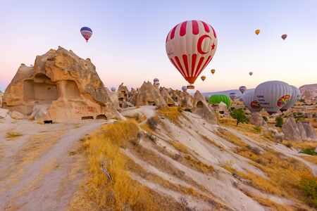 Goreme, Turkey, September 13, 2018 - Hot air balloon flying over rock landscape at Cappadocia, Turkey