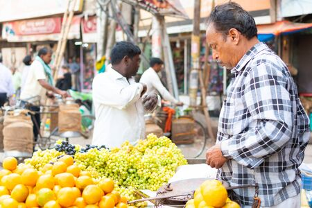 India, Varanasi, Mar 10 2019 - Unidentified vendor man sells and weighs grapes on traditional street food market Reklamní fotografie - 127883595