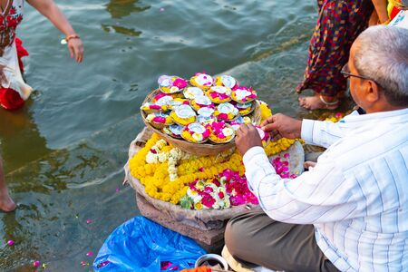 Varanasi, India, 27 Mar 2019 - Indian man selling pooja flowers items for the offering