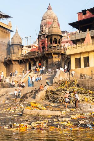 Varanasi, India, 27 Mar 2019 - Ganges River with Manikarnika Ghat, one of the most famous hindu crematory - a corpse is being burned by sacred fire, in the ritual of cremation