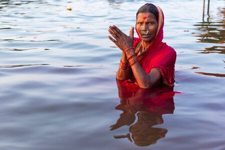 Varanasi, India, 27 Mar 2019 - Hindu woman in sari making offering to the gods in Ganga river at Varanasi, India Reklamní fotografie - 127884663