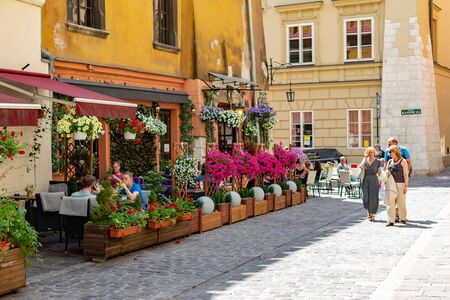 Poland, Krakow, 10 May 2019 - Tiny local cafe in center of Krakow, flowers decorating it, cobbled streets full of people, Krakow, Poland