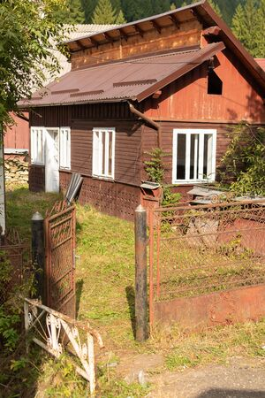 Typical rural architecture of Romania countryside with sunny green courtyard and tiled roof