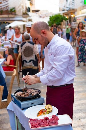 ALCUDIA, SPAIN - July 8, 2019: Restaurant tables on street with tourists in seaside Alcudia old town, Mallorca island, Spain. Redakční