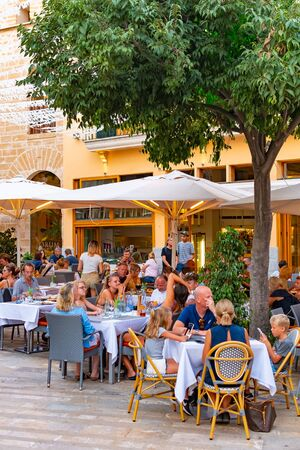 ALCUDIA, SPAIN - July 8, 2019: Restaurant tables on street with tourists in seaside Alcudia old town, Mallorca island, Spain
