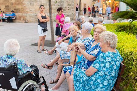 Palma de Mallorca Spain, 8 July 2019 - Senior tourists enjoying sightseeing in old narrow of Alcudia Town, Mallorca Redakční