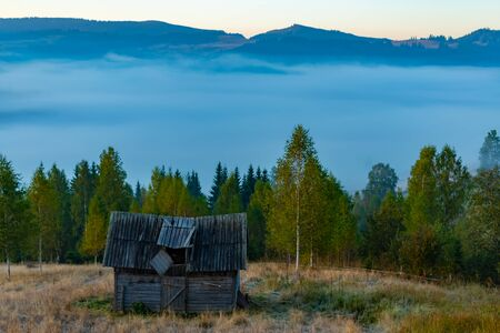 Beautiful autumn landscape during sunrise with old hut and fog in valley with mountains, Romania.