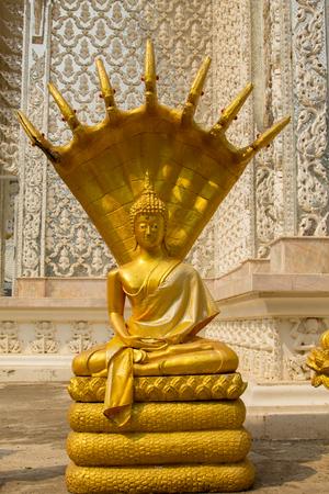 golden Buddha statue,Buddha and seven serpent heads at Wat Mai Kham Wan temple, Phichit, Thailand.