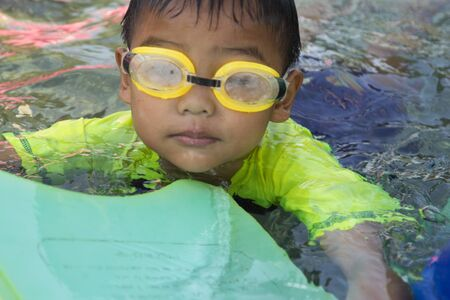 Children swimming. Boy Practice Swimming. Activities on the pool, playing in water, happiness and holiday.