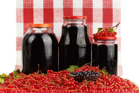 Home canning jars of berry fruits and heap of fresh red currant