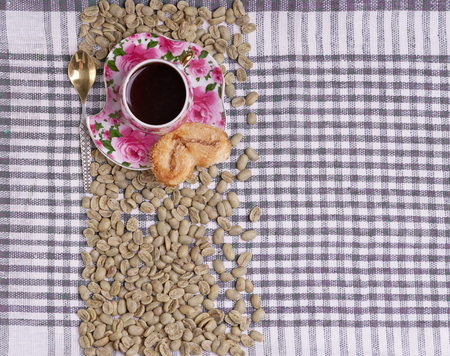 Cup of coffee and green coffee beans on tablecloth. Maragogype.