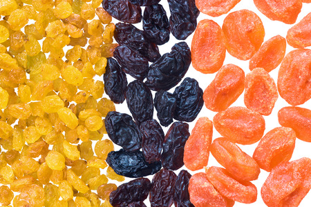 Vivid dried fruits. Dried kumquat, golden and black raisins isolated on white background.