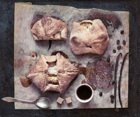Cup of coffee and flaky pastries on parchment.