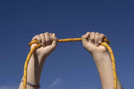 permanence: Two hands with an orange rope on sky background