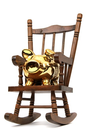 old wooden rocking chair and golden piggy bank on white photo