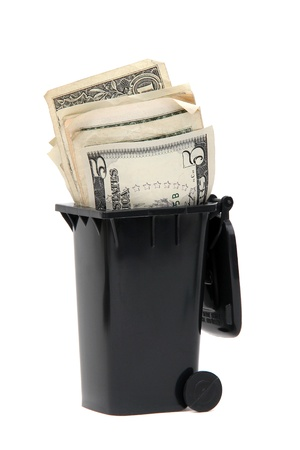bank notes in black rubbish bin on white photo