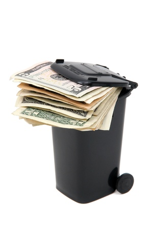 rubbish bin: batch of bank notes in black rubbish bin on white Stock Photo