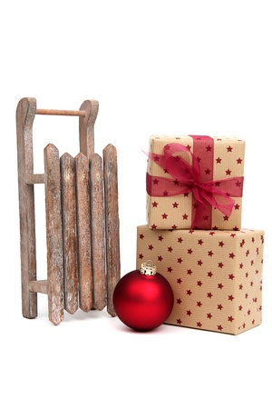 old wooden sledge with christmas presents on white photo