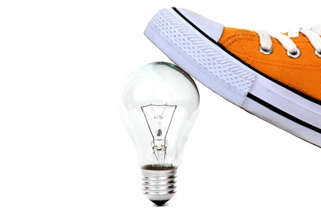 lamp bulb under yellow sneaker on white Stock Photo - 12291244
