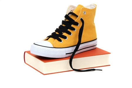 Yellow sneaker on book photo