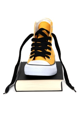 Yellow sneaker on black book photo
