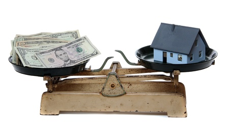 house and dollar notes on scale