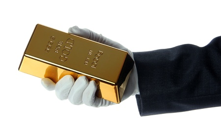 hand with glove holding a gold bullion photo