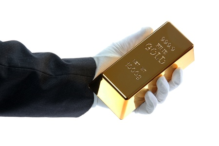 hand with glove holding a gold bar Stock Photo